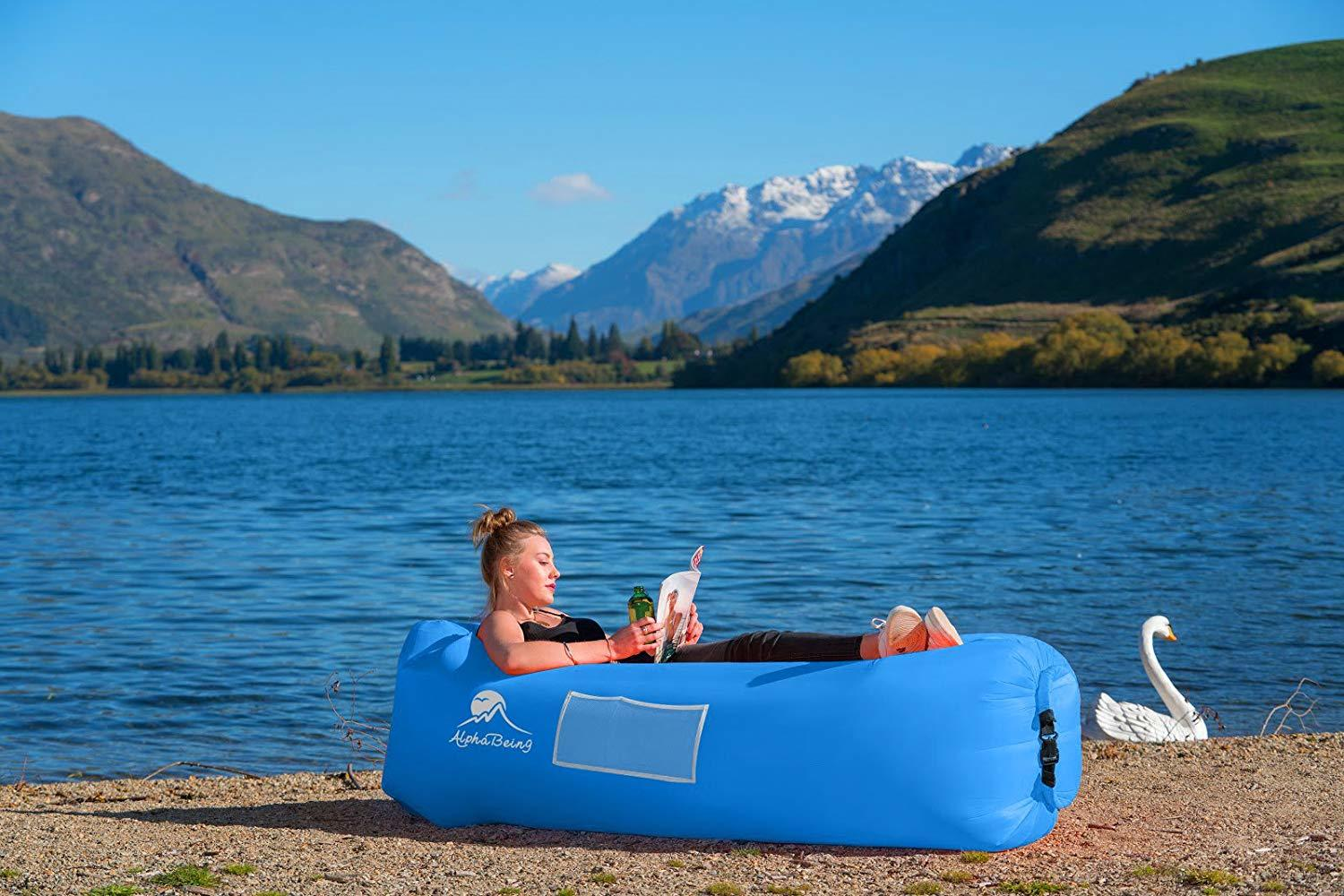 woman laying down in the inflatable lounger while reading a magazine beside a river