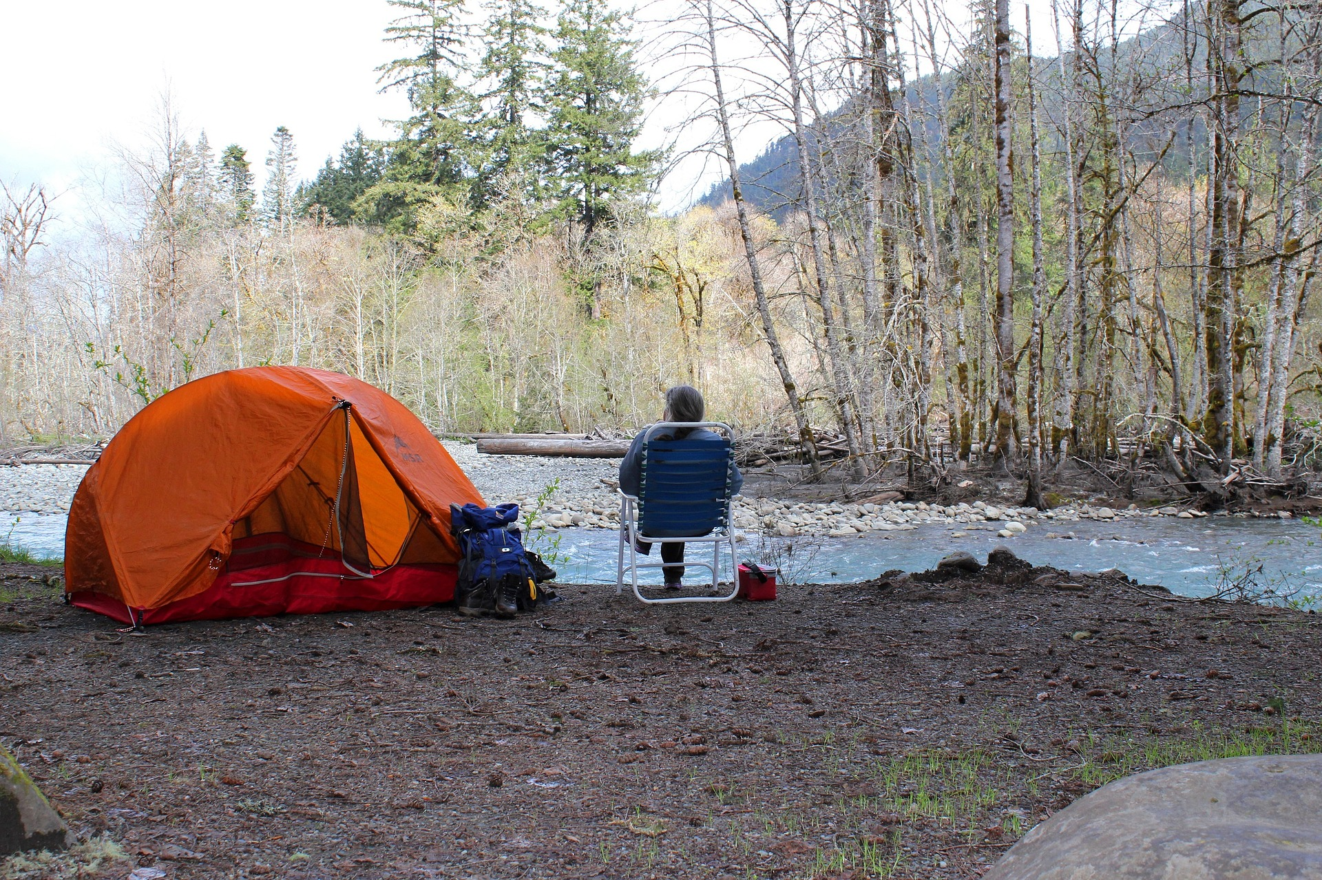 Man sitting in front of the river and beside him is his camping equipment
