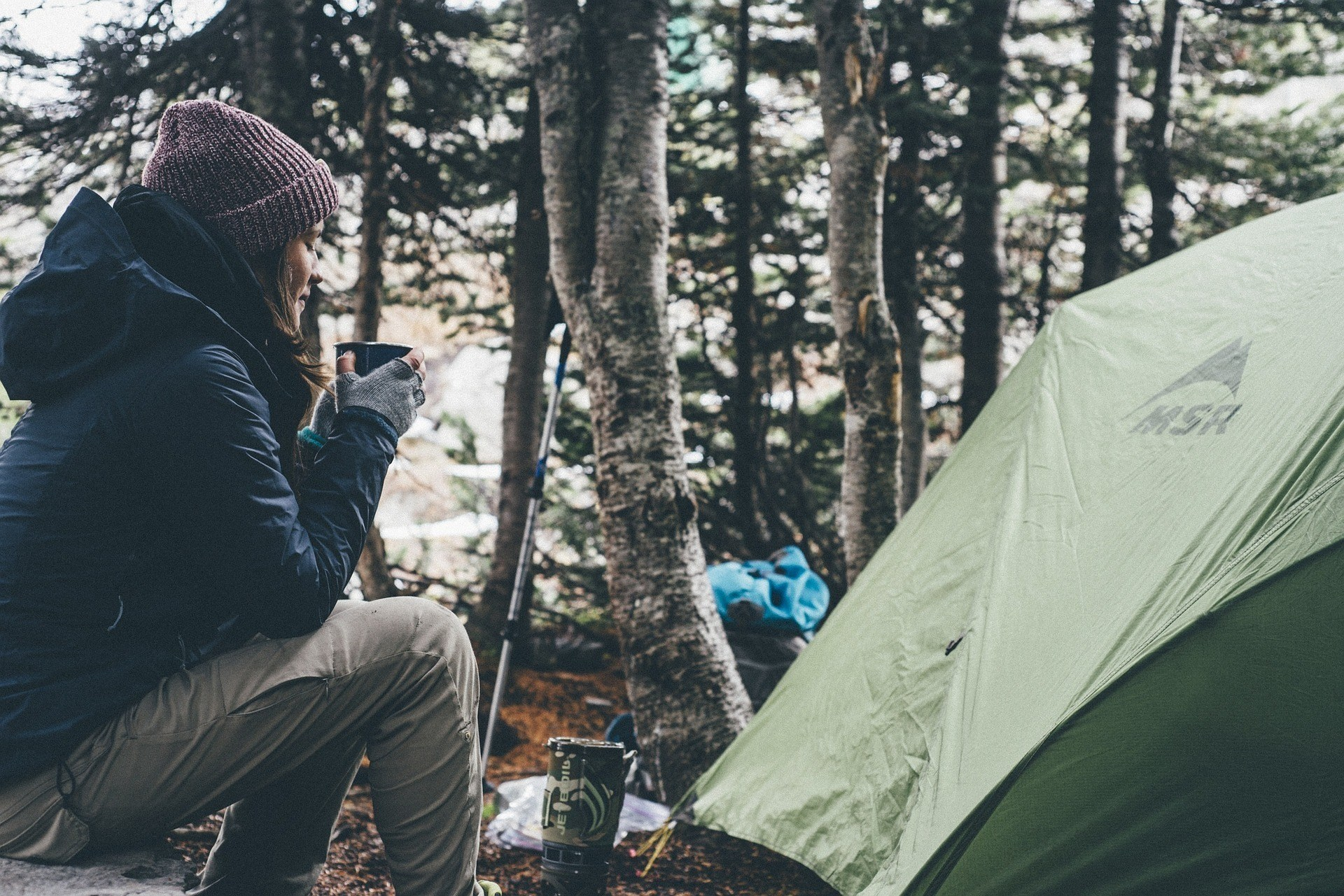 Woman drinking coffee is wearing a cap and sweater for the cold weather in the forest and beside her is her camping equipment