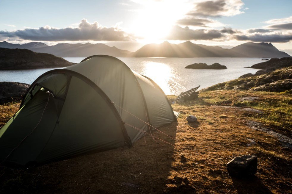Stealth camping shown by a lake in a small tent